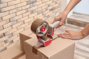 This image shows someone tapeing a box closed.