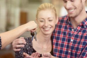Photo of realtor handing keys to new homeowners