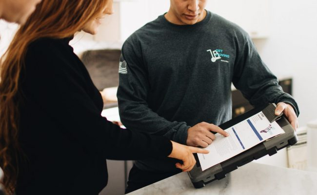 This picture shows a Get Moving professional showing a customer the details of the moving contract.