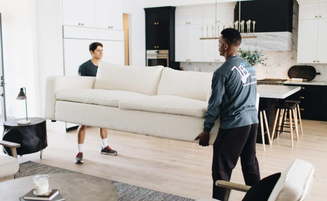 Image: Get Moving crew members moving a sofa.