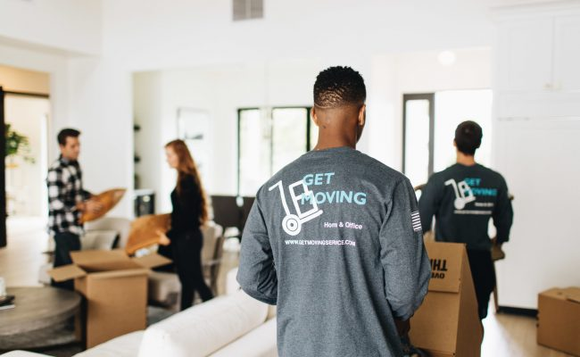 Image: Get Moving crew moving boxes in a house.